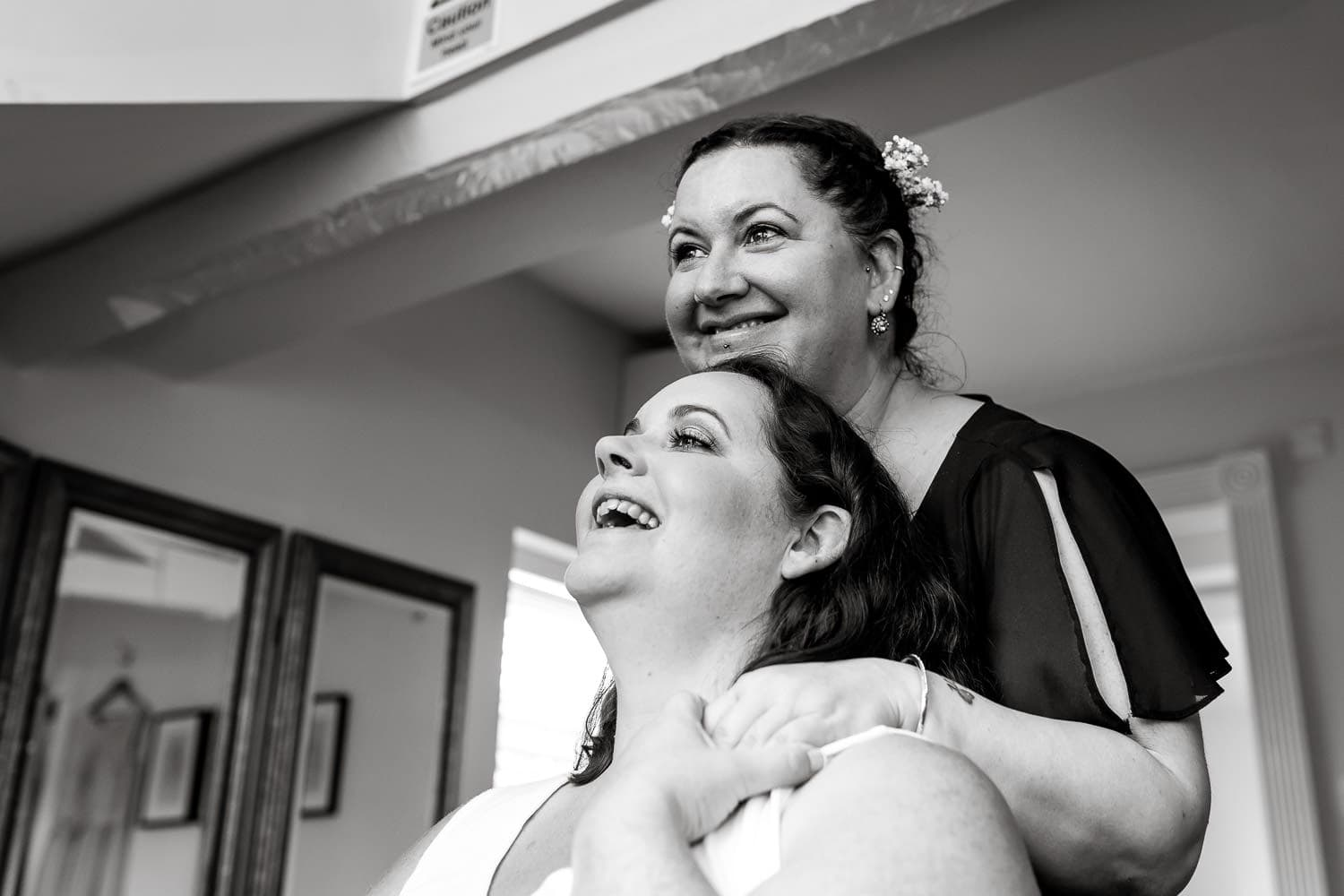 bride and sister share a tender moment prior to warwick house wedding starting