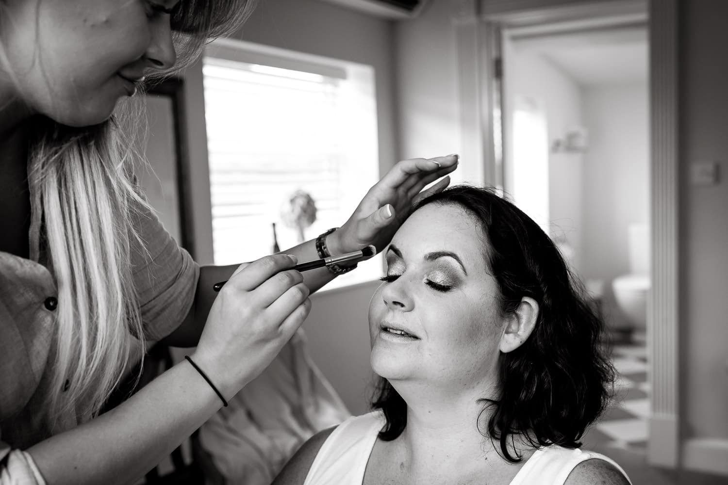 bride as eye liner applied prior to wedding ceremony at warwick house wedding venue