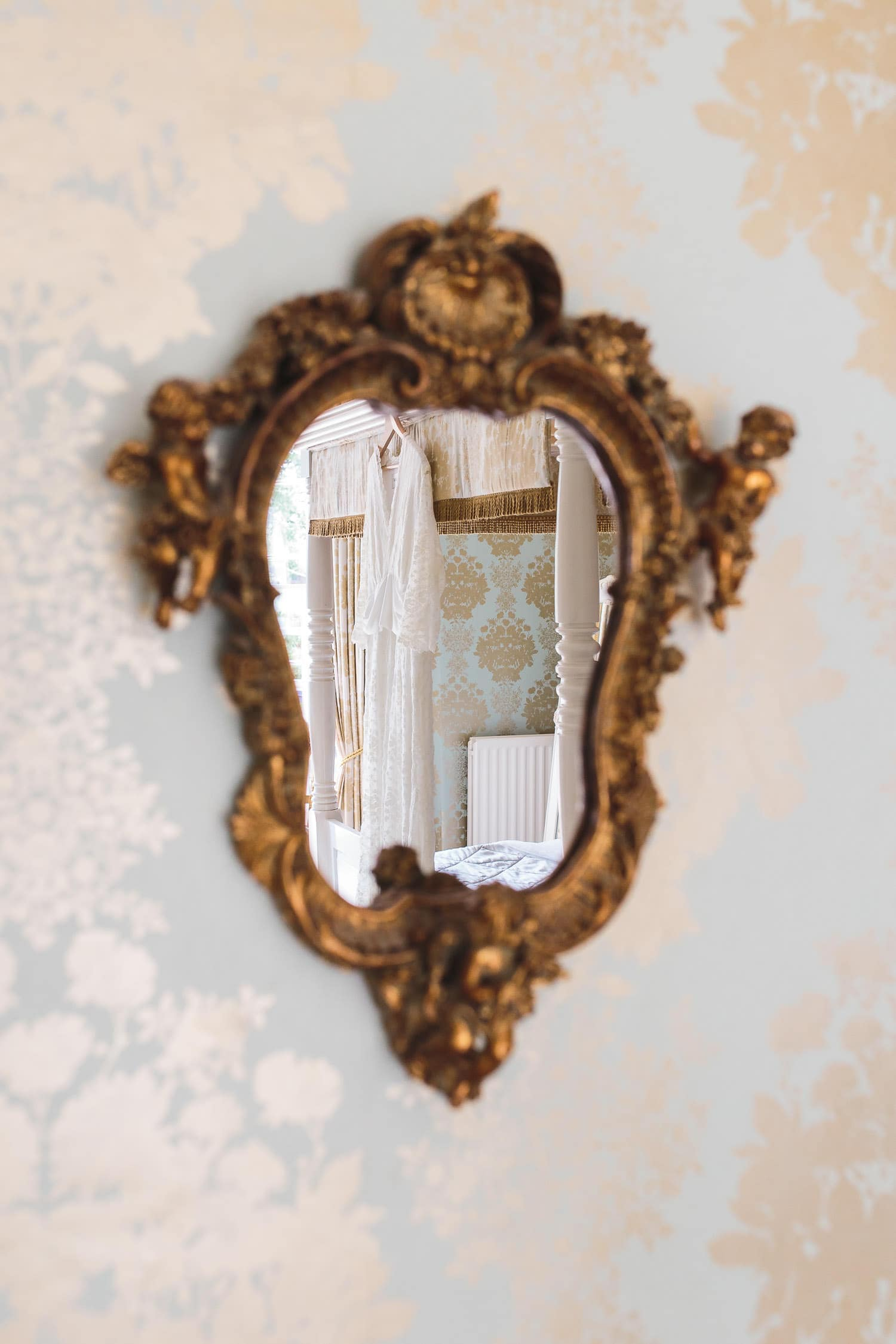 reflection of wedding dress in mirror on the wall at warwick house wedding venue in southam