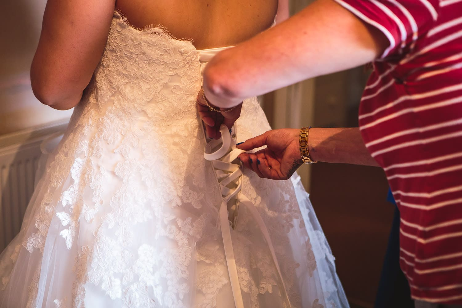 mother helps daughter put on wedding dress by chapter one photography
