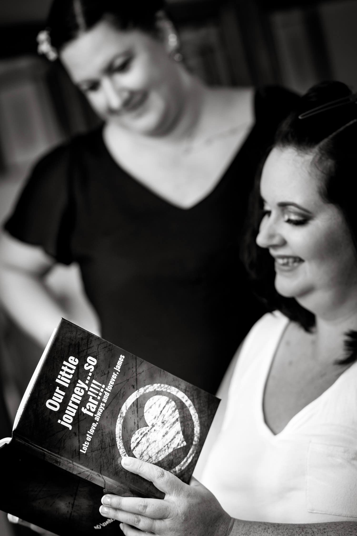 bride and sister enjoy reading a book before the start of a warwick house wedding
