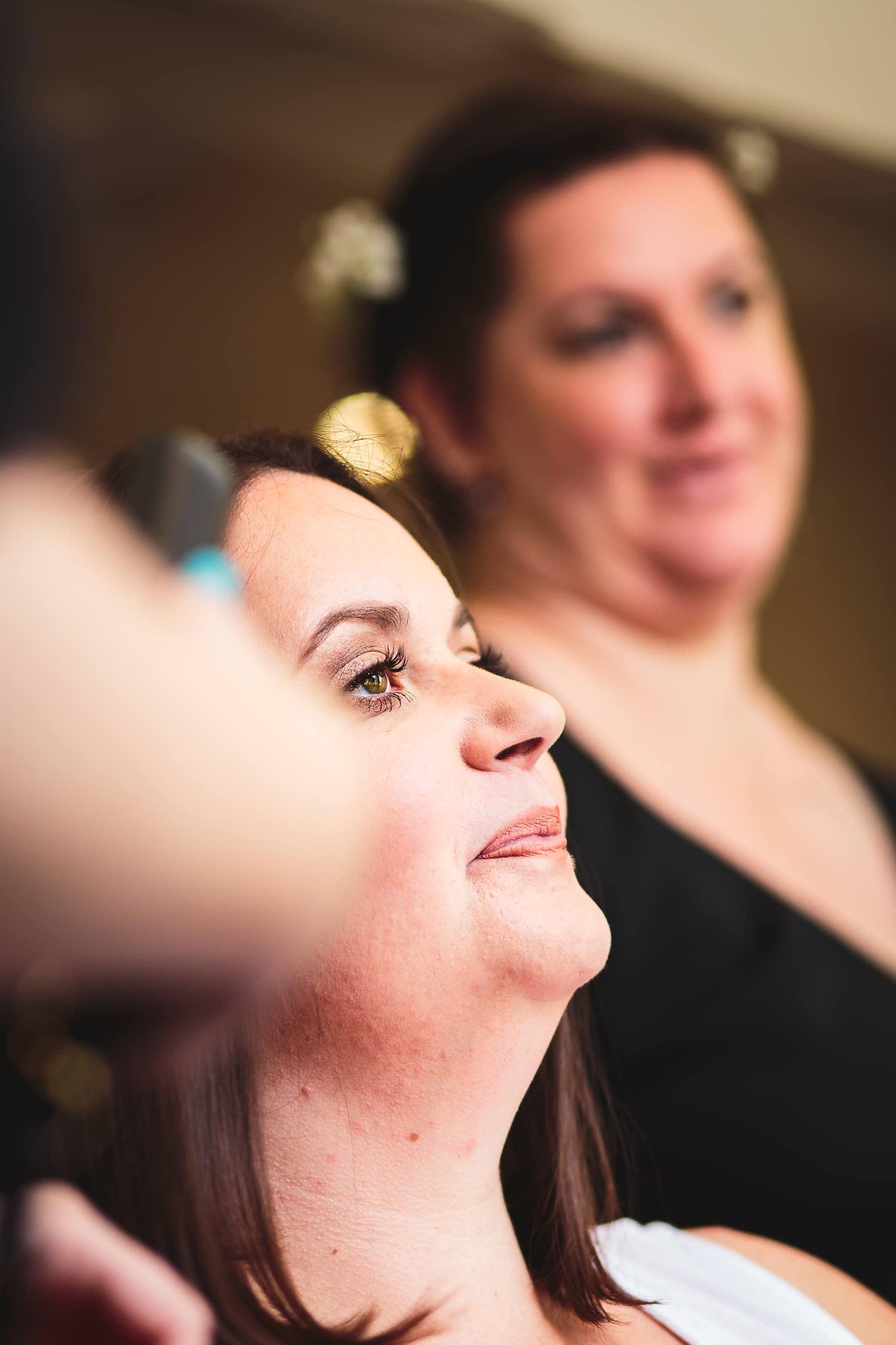 bride has hair straightend while sister looks on beforewarwick house wedding