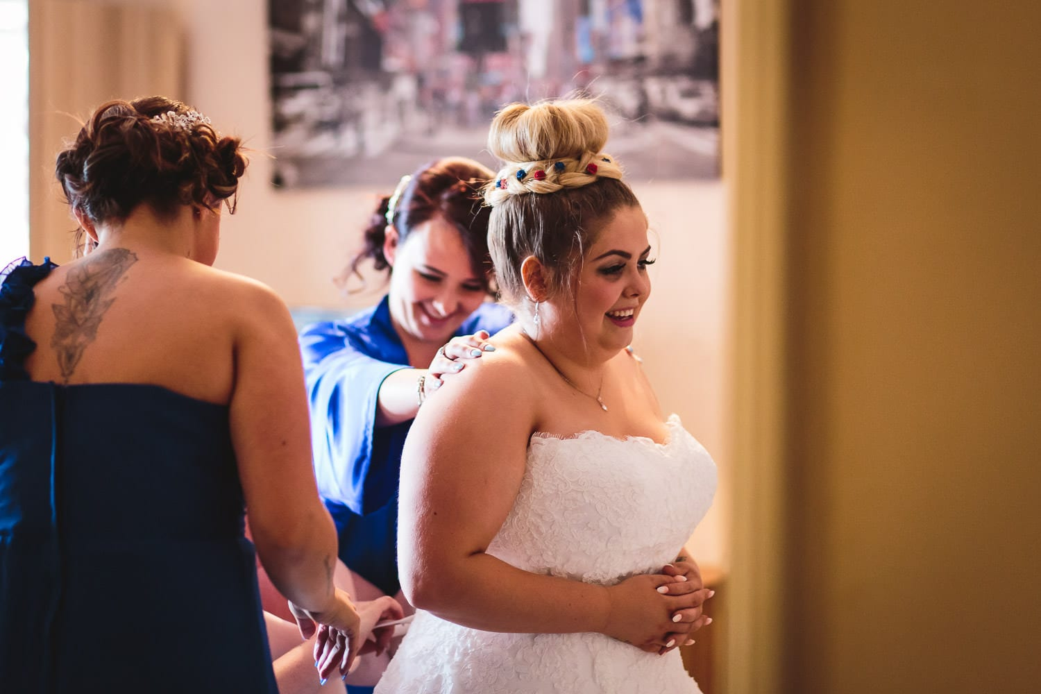 bridesmaids help bride to squuze into wedding dress by chapter one photography