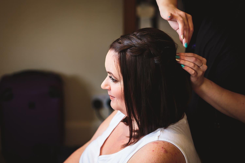bride has hair prepared before warwick house wedding