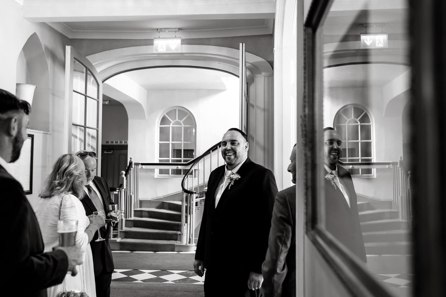 groom greets and chats with guests at warwick house wedding