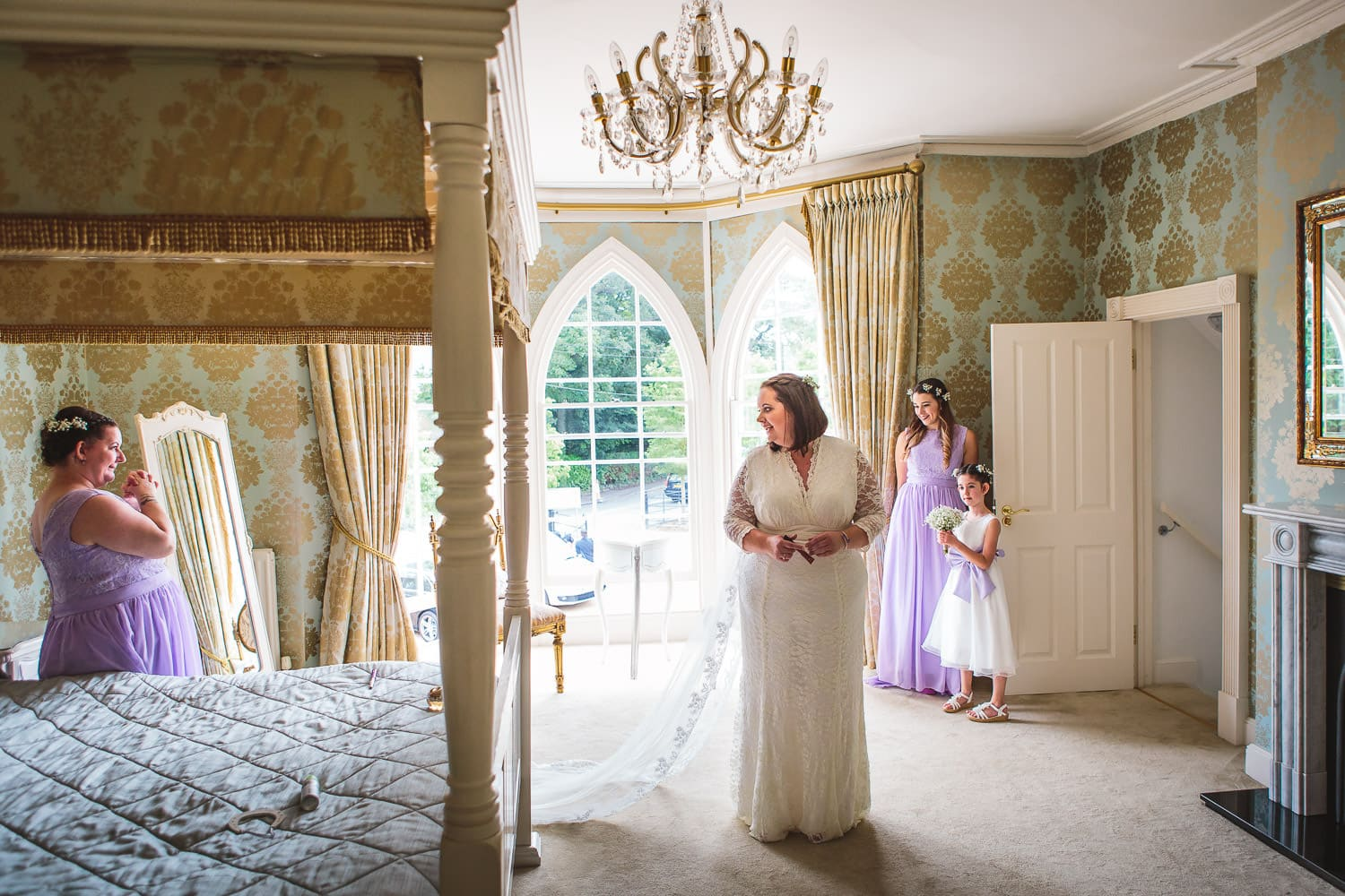 bridal party help to get bride ready in beautiful room at warwick house wedding