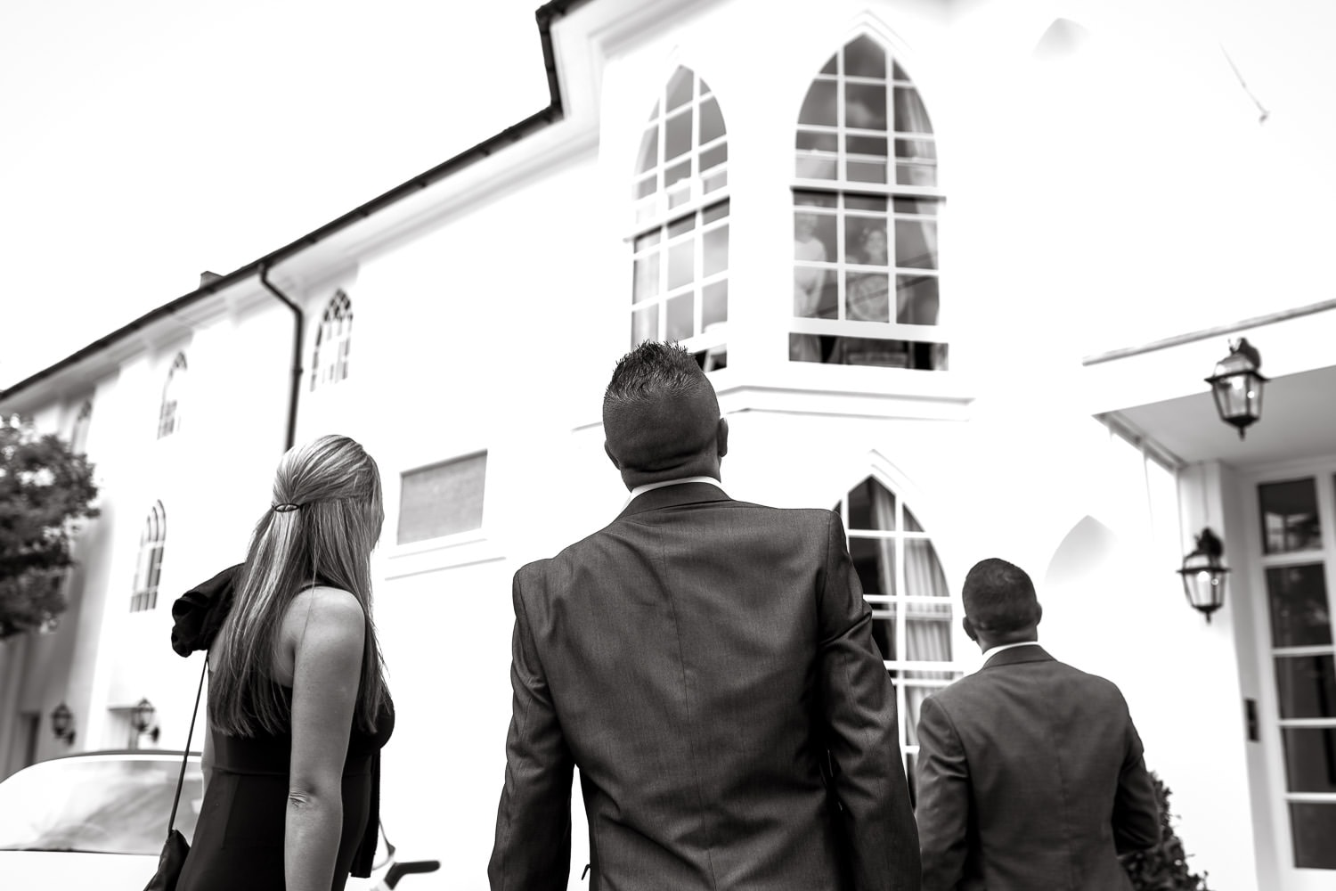 candid picture of guests looking up towards bridal room at warwick house wedding