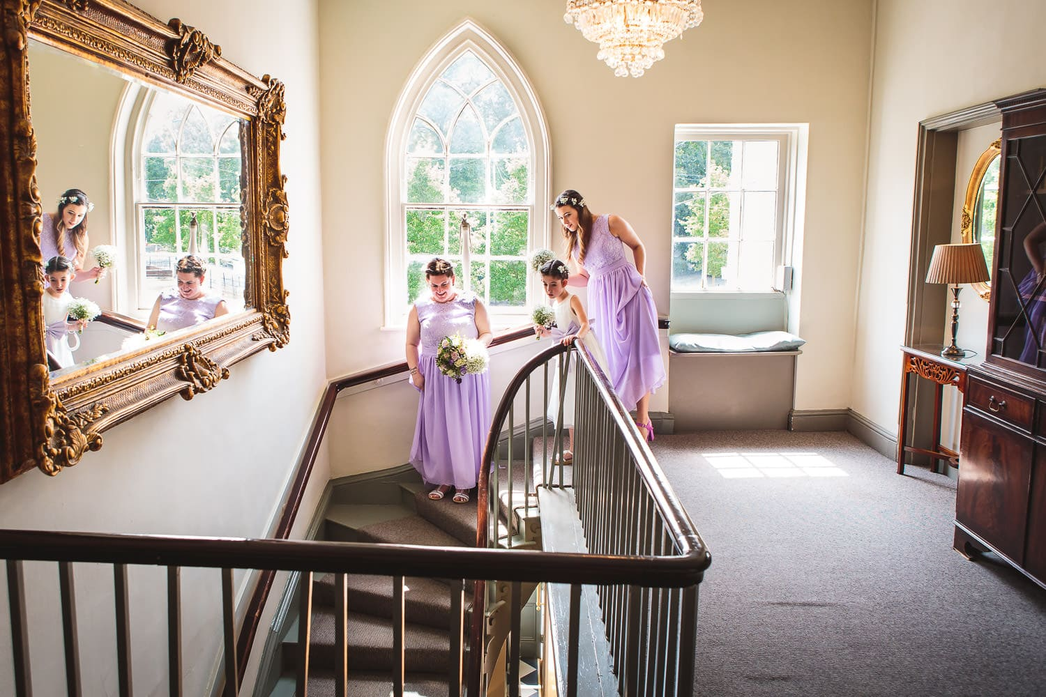 bridal party peeks down stairs at warwick house wedding in southam