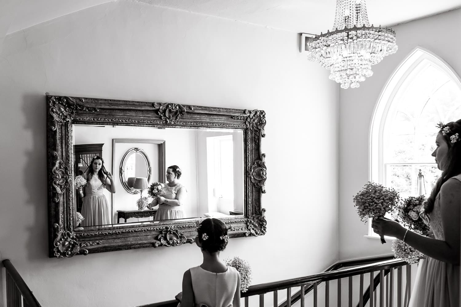 Bridal party catches relection in mirror at stunning warwick house wedding venue