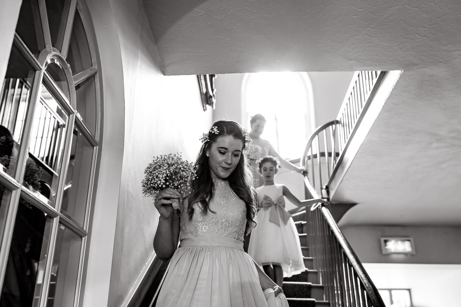 bridal party make their way down the stairs at magnificant warwick house wedding