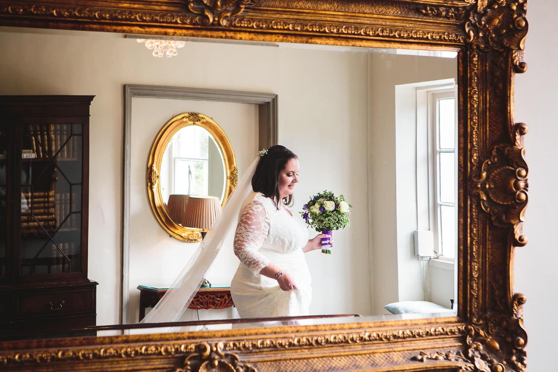 bride captured reflection in mirror at warwick house wedding