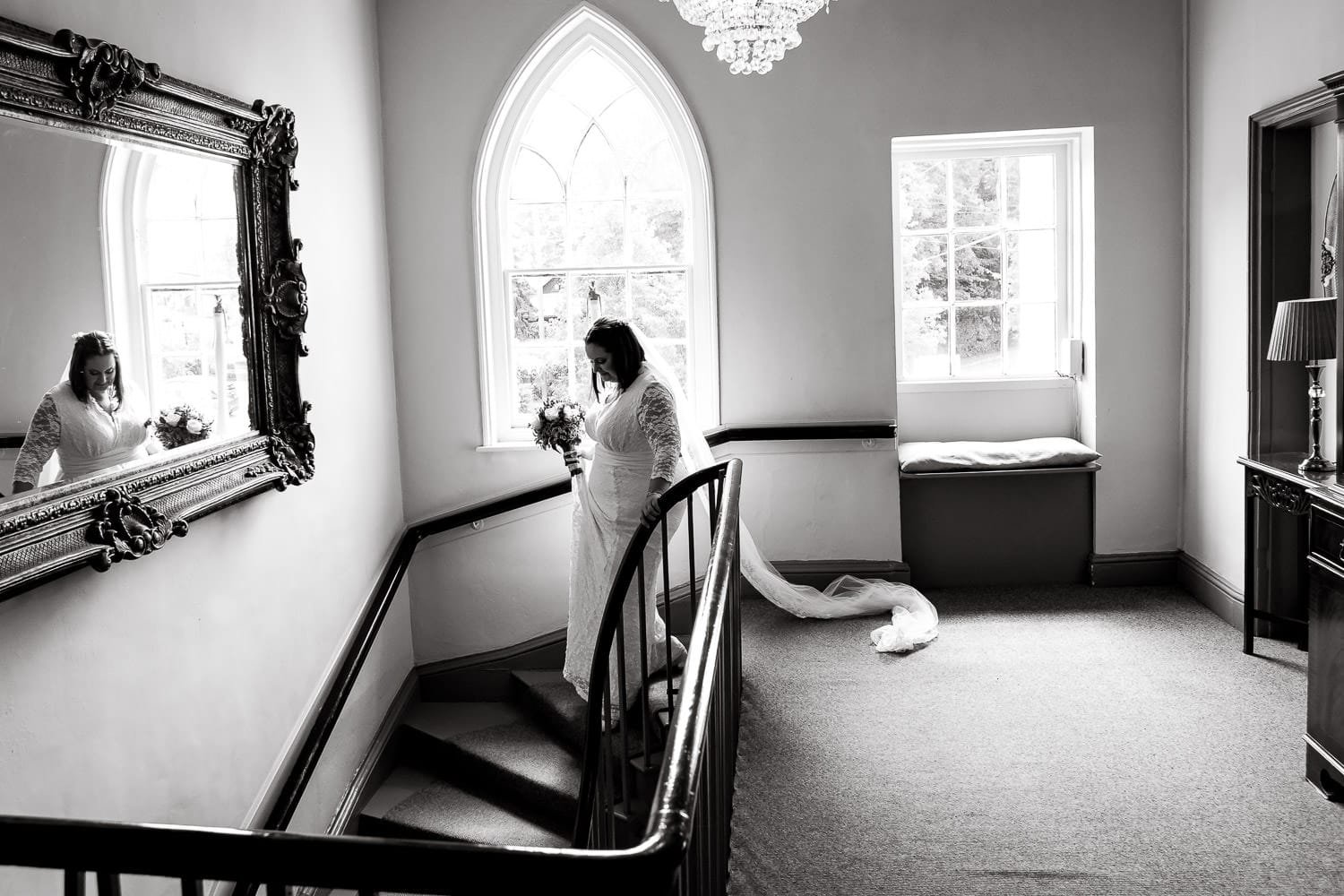 bride walks down the stairs to ceremony at warwick house wedding