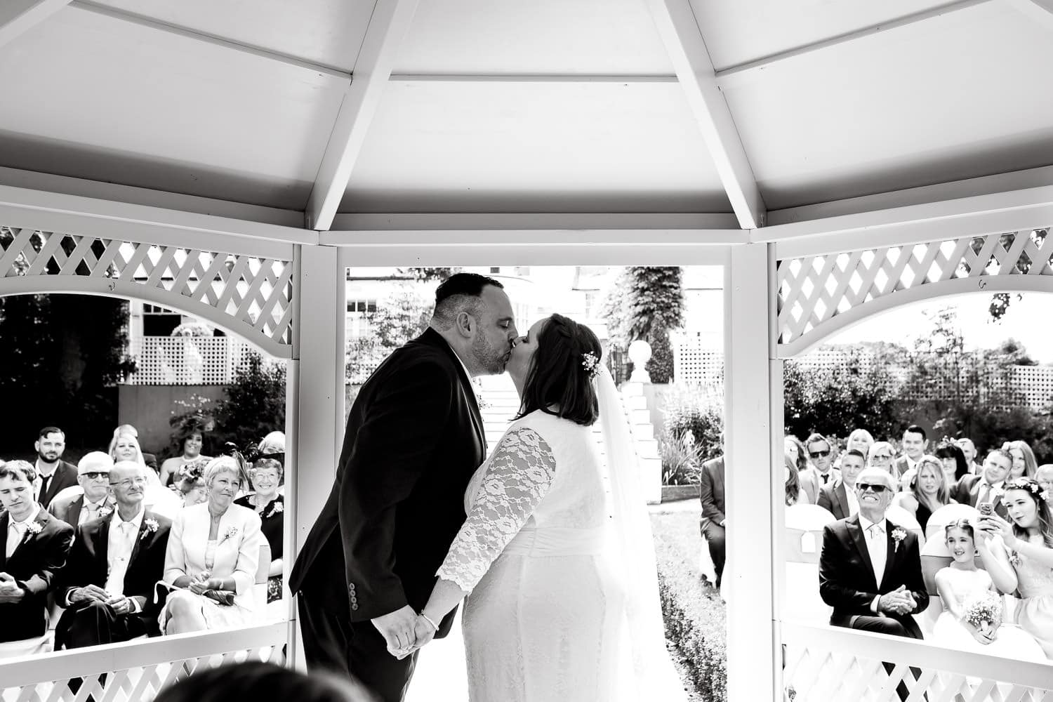 first kiss by bride and groom during warwick house wedding ceremony