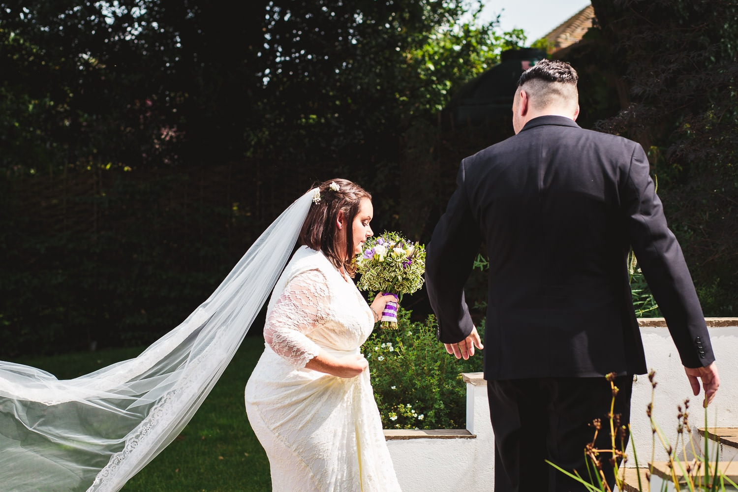 groom helps bride up the staris at warwick house wedding in southam