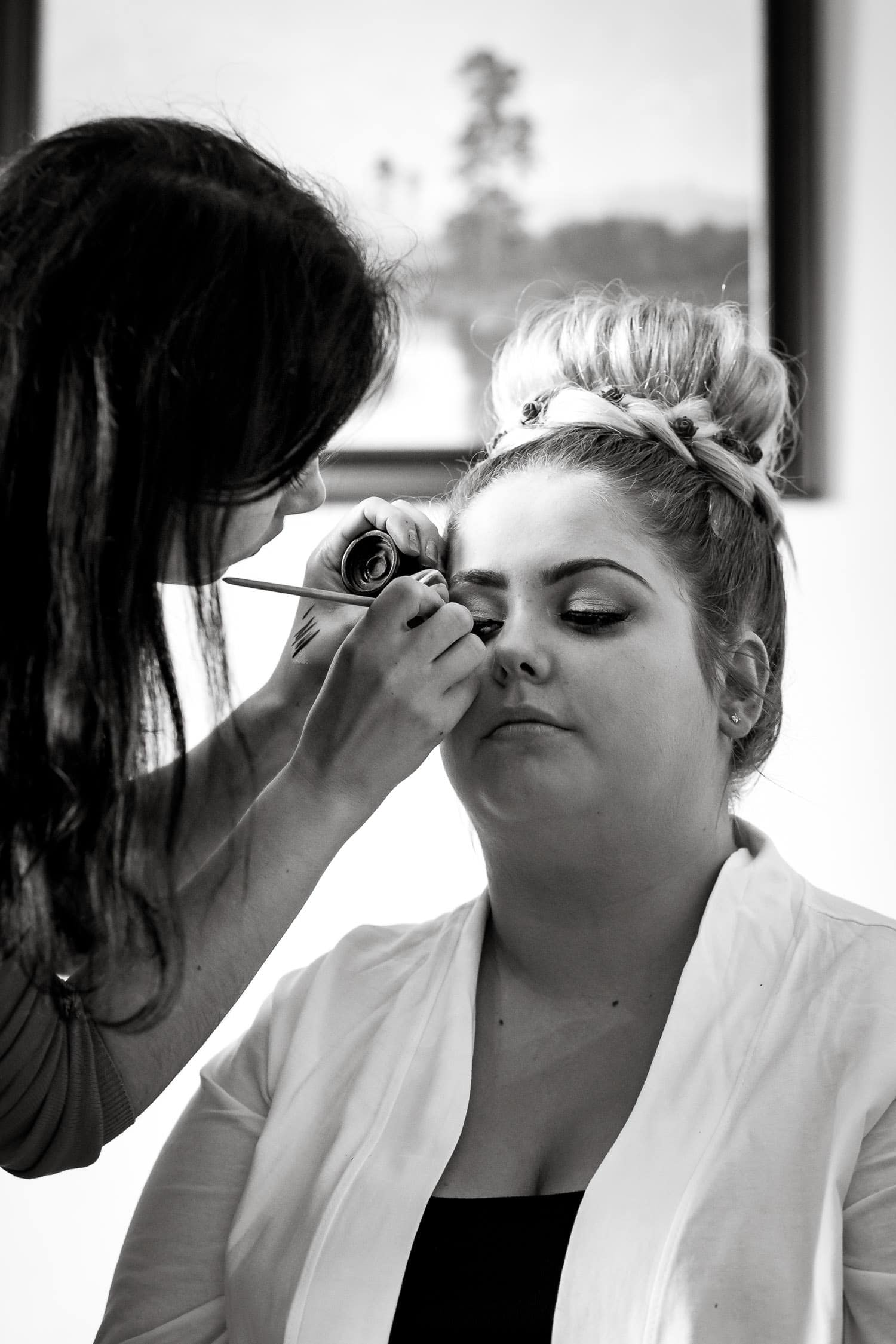 bride has makeup applied for wedding day captured by chapter one photography