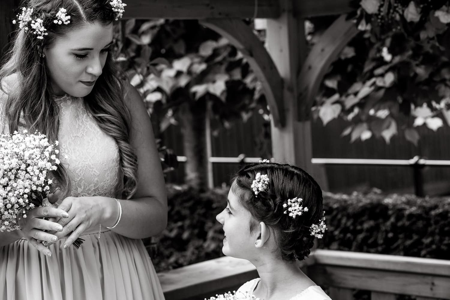 bridesmaid and flowergirl smile to each other at warwick house wedding