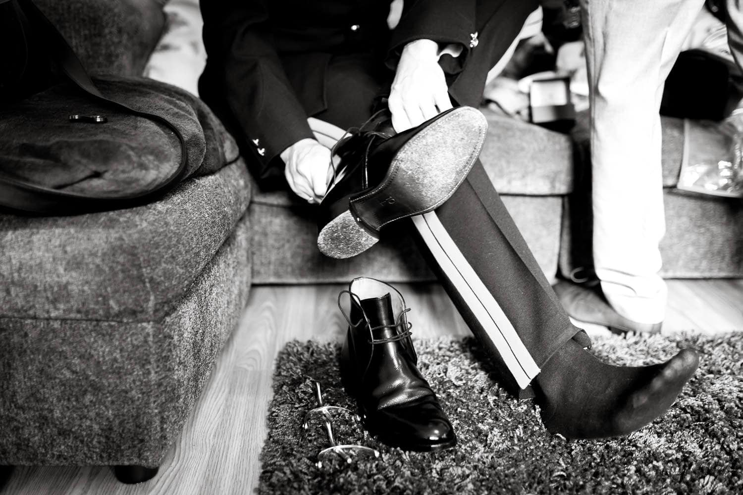 groom puts on shoes by chapter one photography