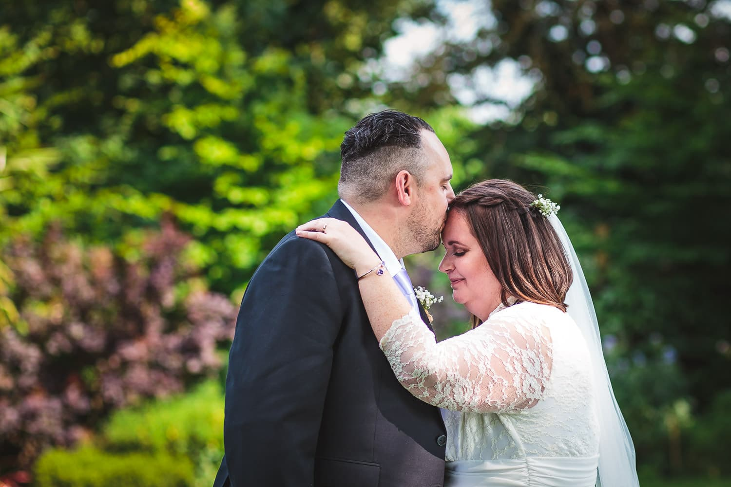 groom gently kisses brides forehead during portait session at warwick house wedding