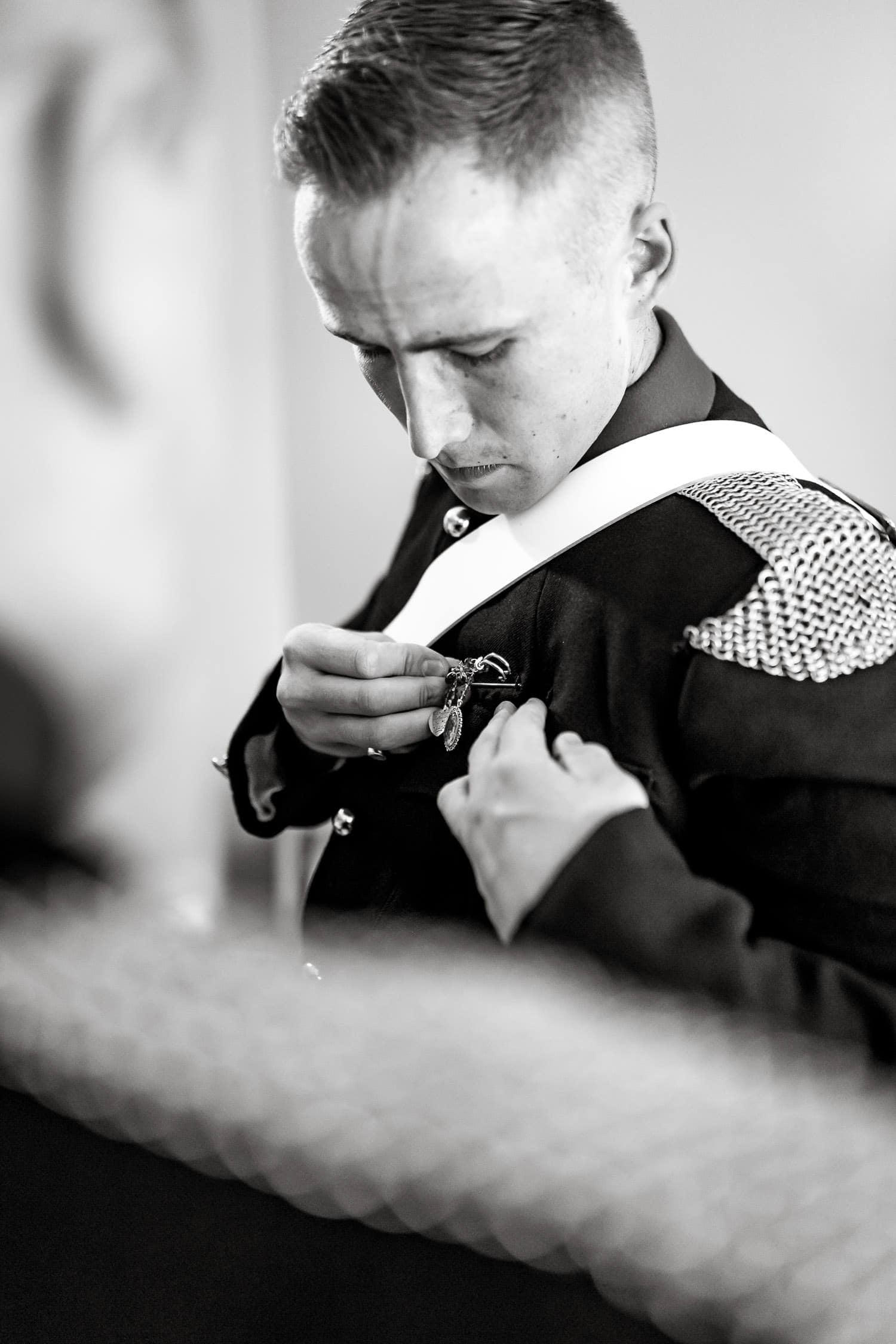 groom puts broach onto jacket by chapter one photography