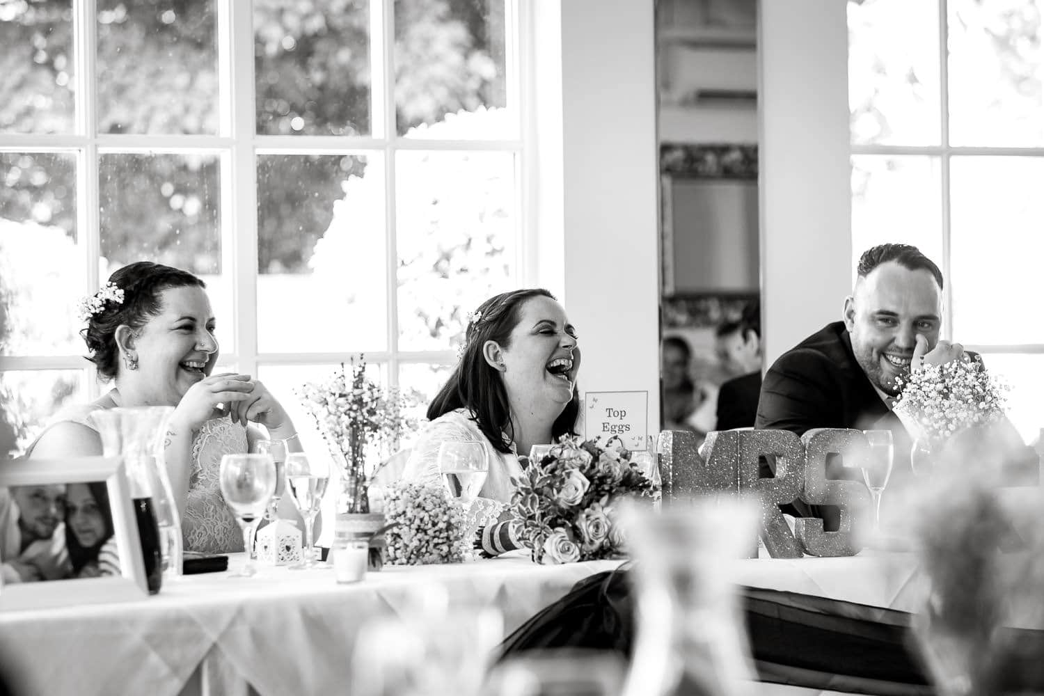 happy bride laughs during speeches at warwick house wedding