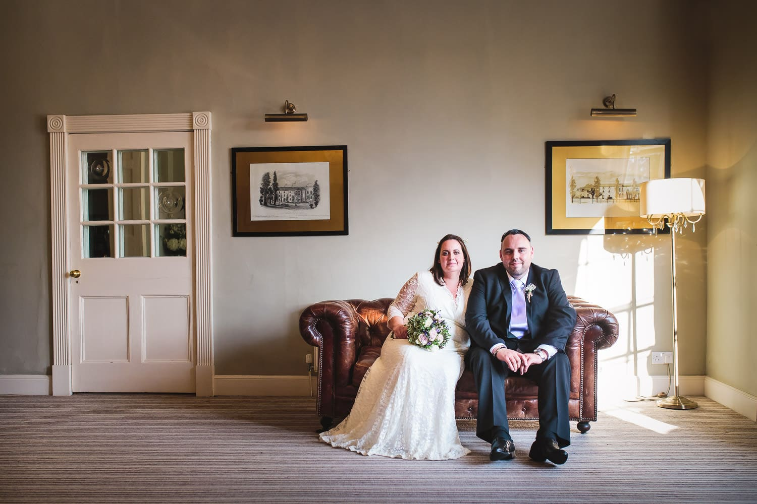 bride and groom pose in lounge at warwick house wedding in southam