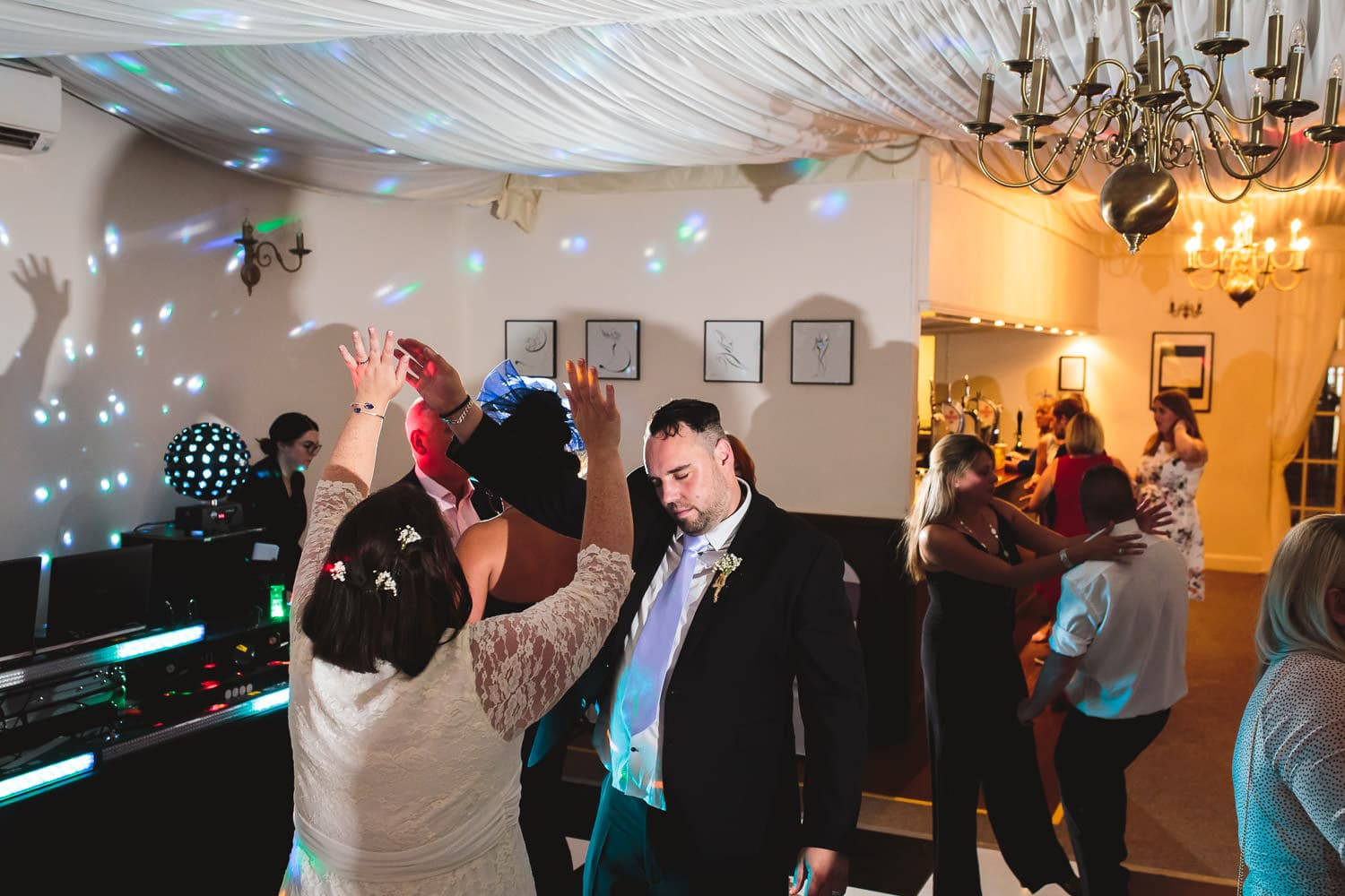 couple dance with hands in the air during eveing reception at warwick house wedding