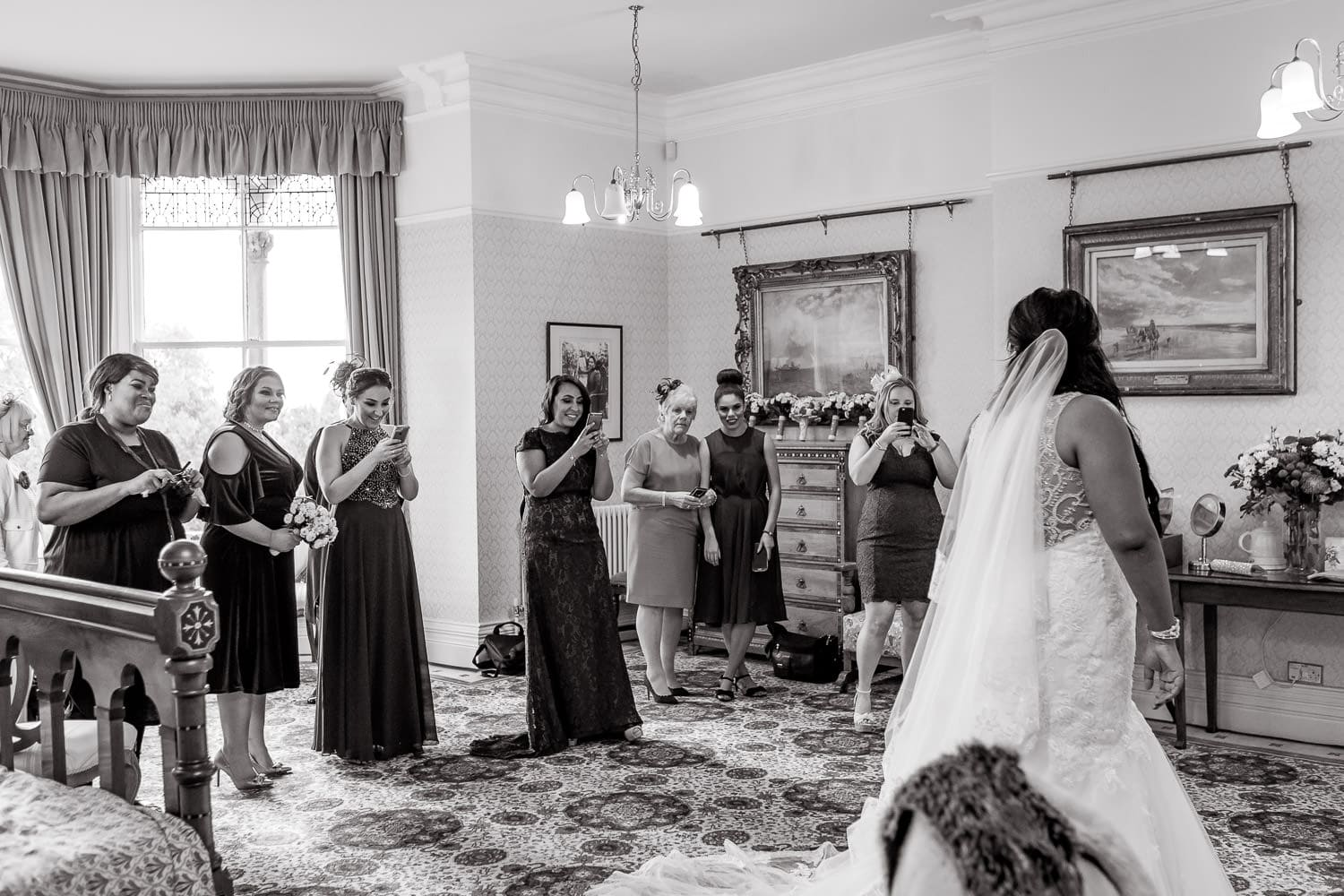 bride poses for bridal party + friends + family