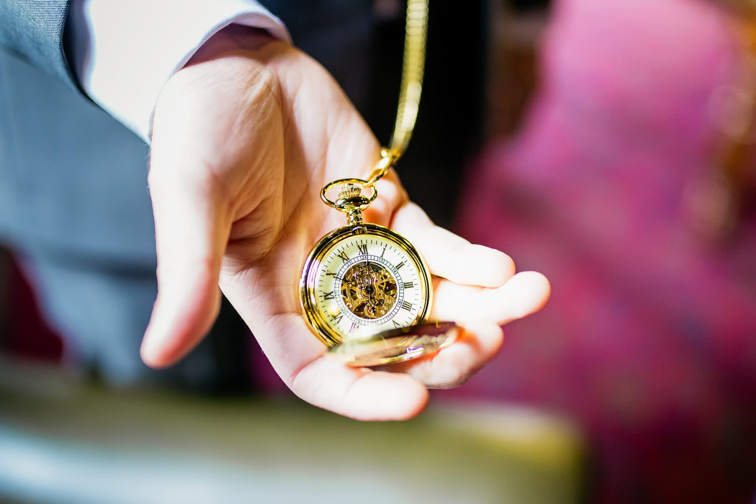 groom holds a pocket watch in his hand
