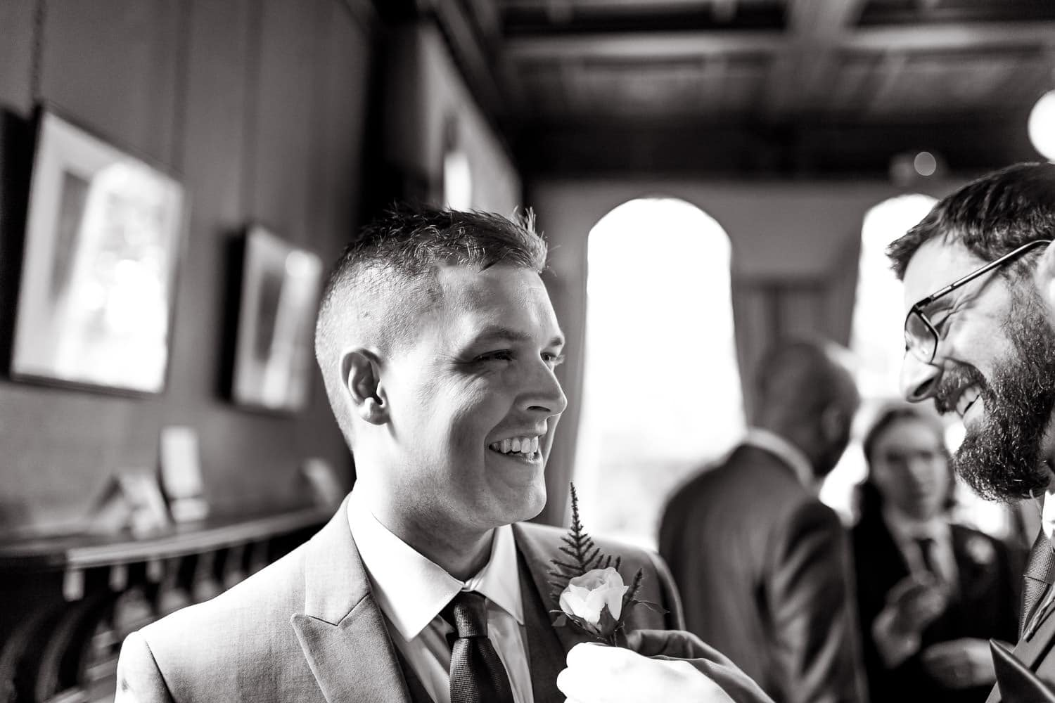 best man helps groom with boutonnière