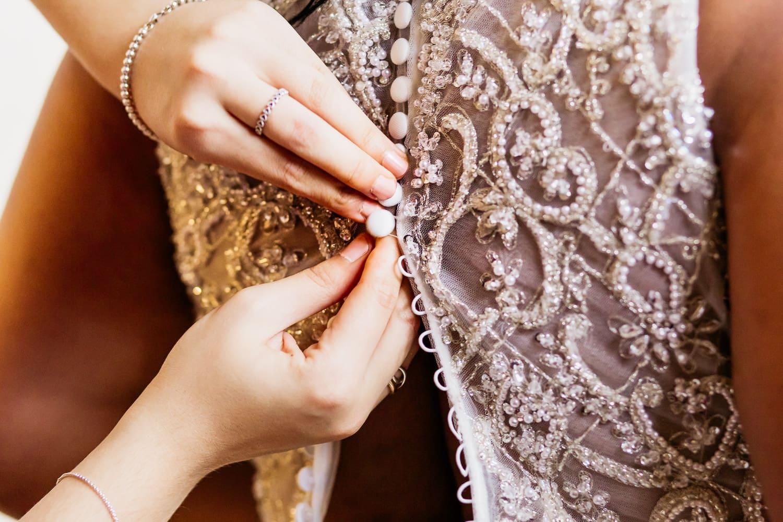 bridesmaid helps bride button her dress