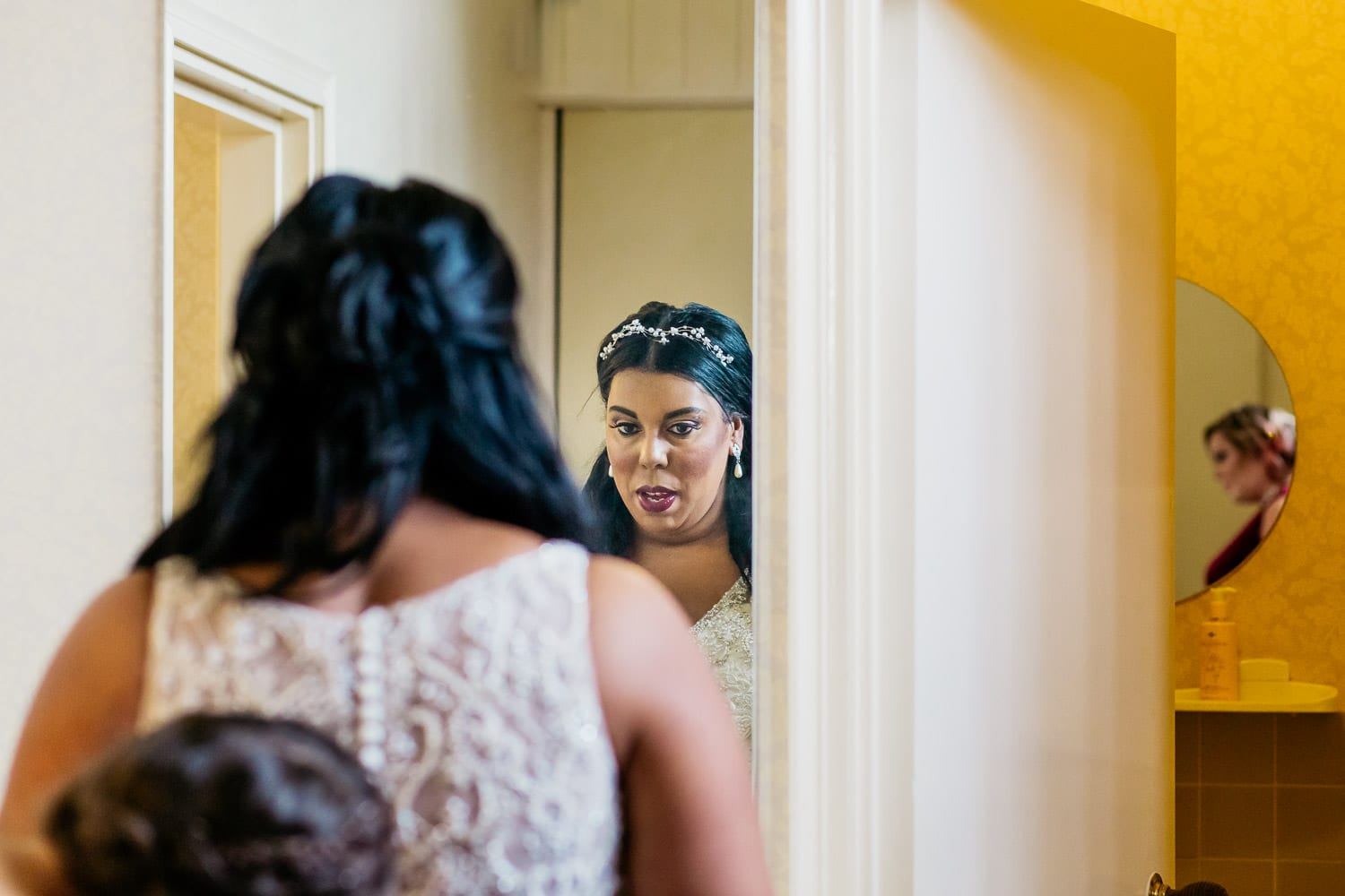 bride looks into a mirror with visible reflection