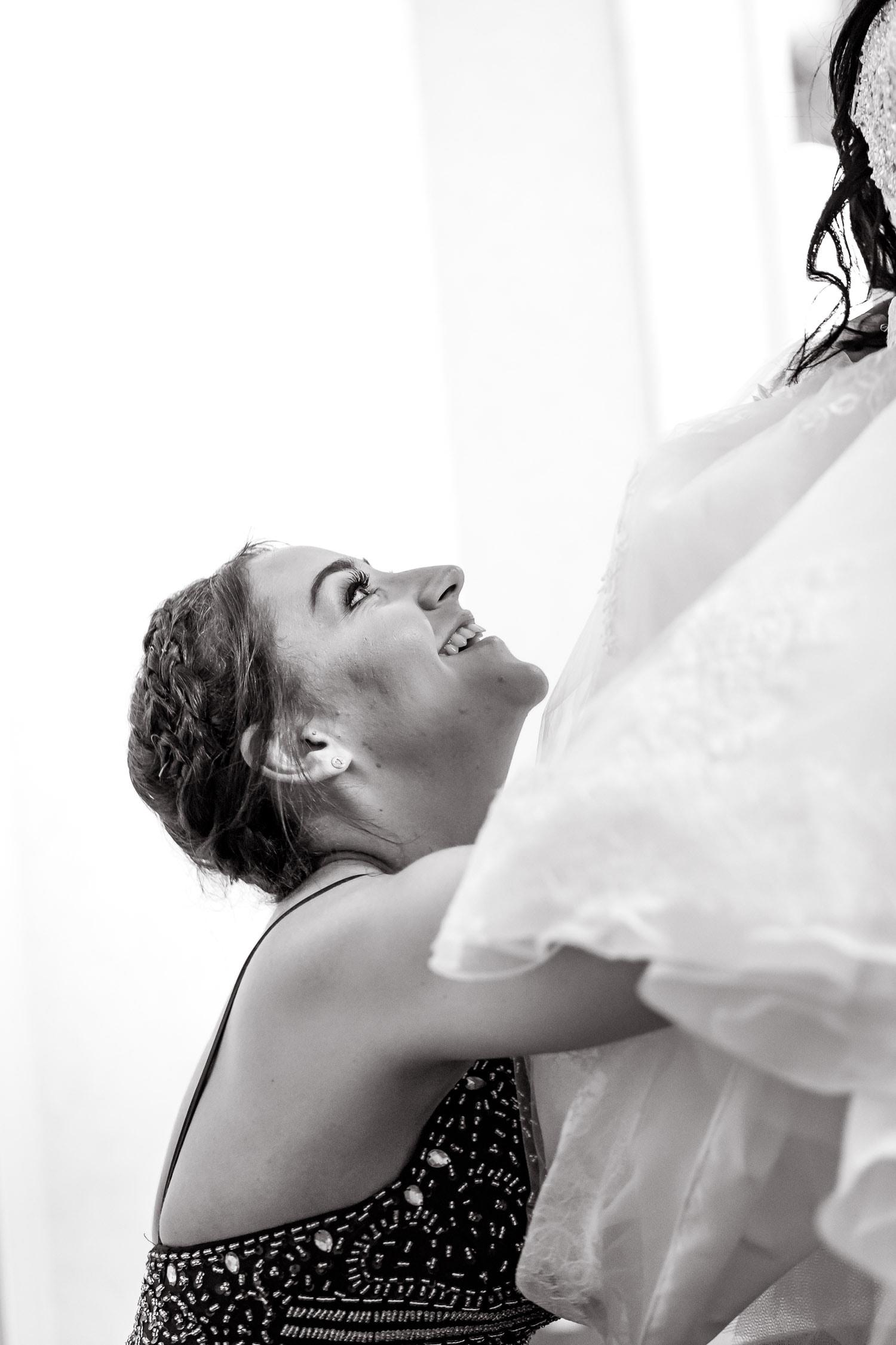bridesmaid helps bride fix her dress