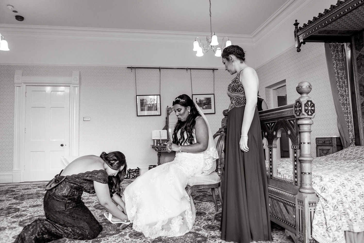 bridesmaid helps bride to put on shoes