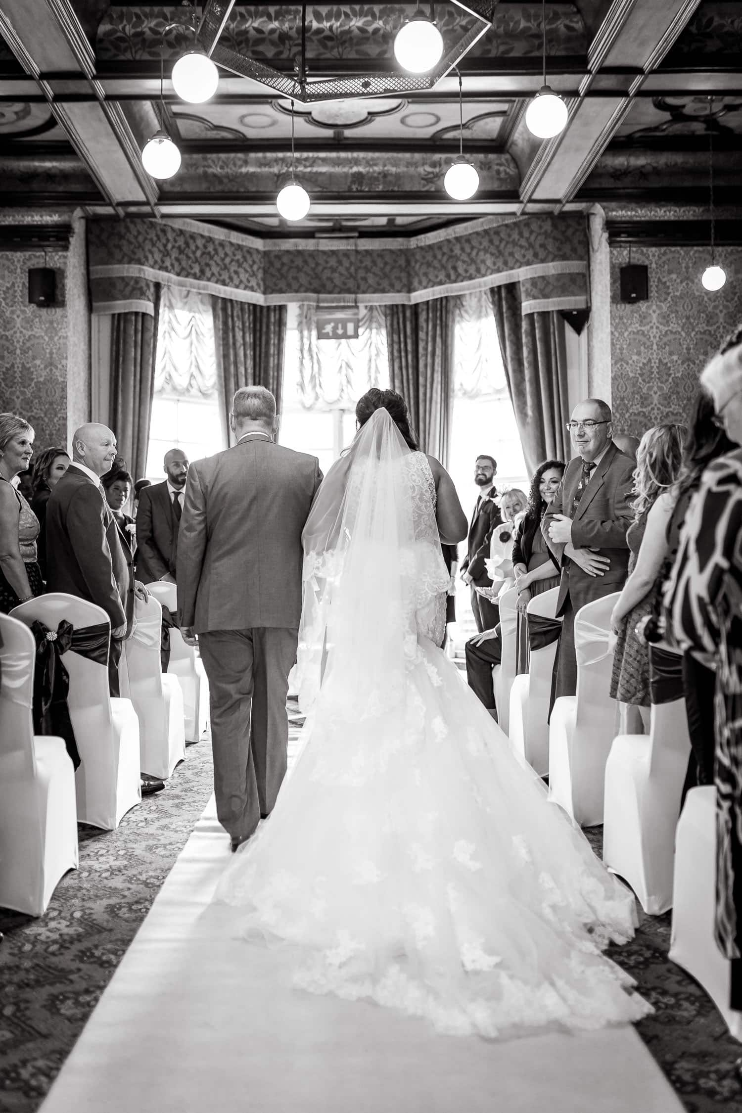 father leads bride down the aisle in wedding ceremony