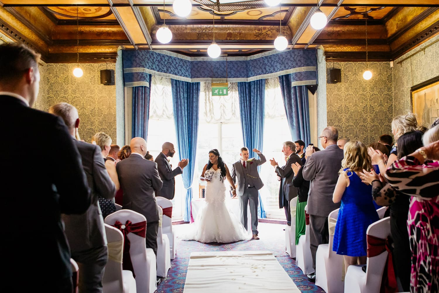 Highbury hall wedding photography captures groom punching the air in excitement after wedding ceremony