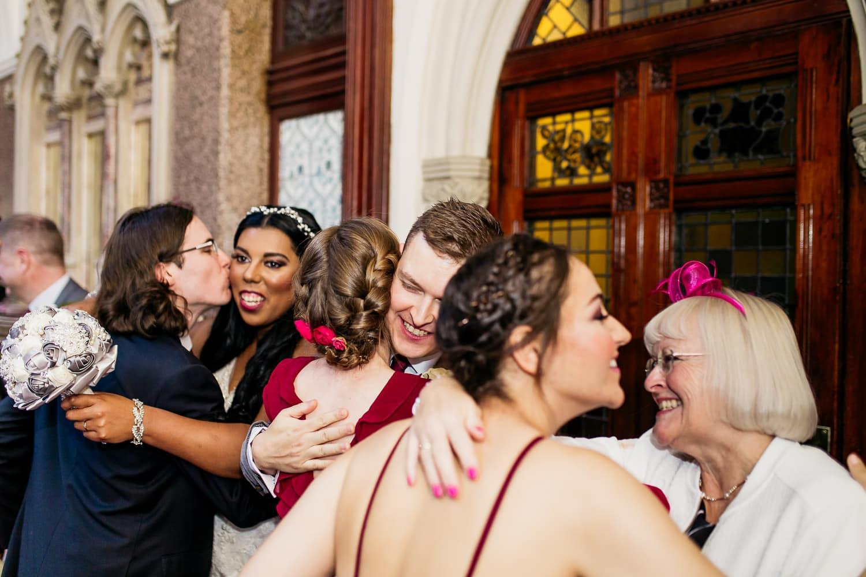 groom hugs a wedding guest during receiving line