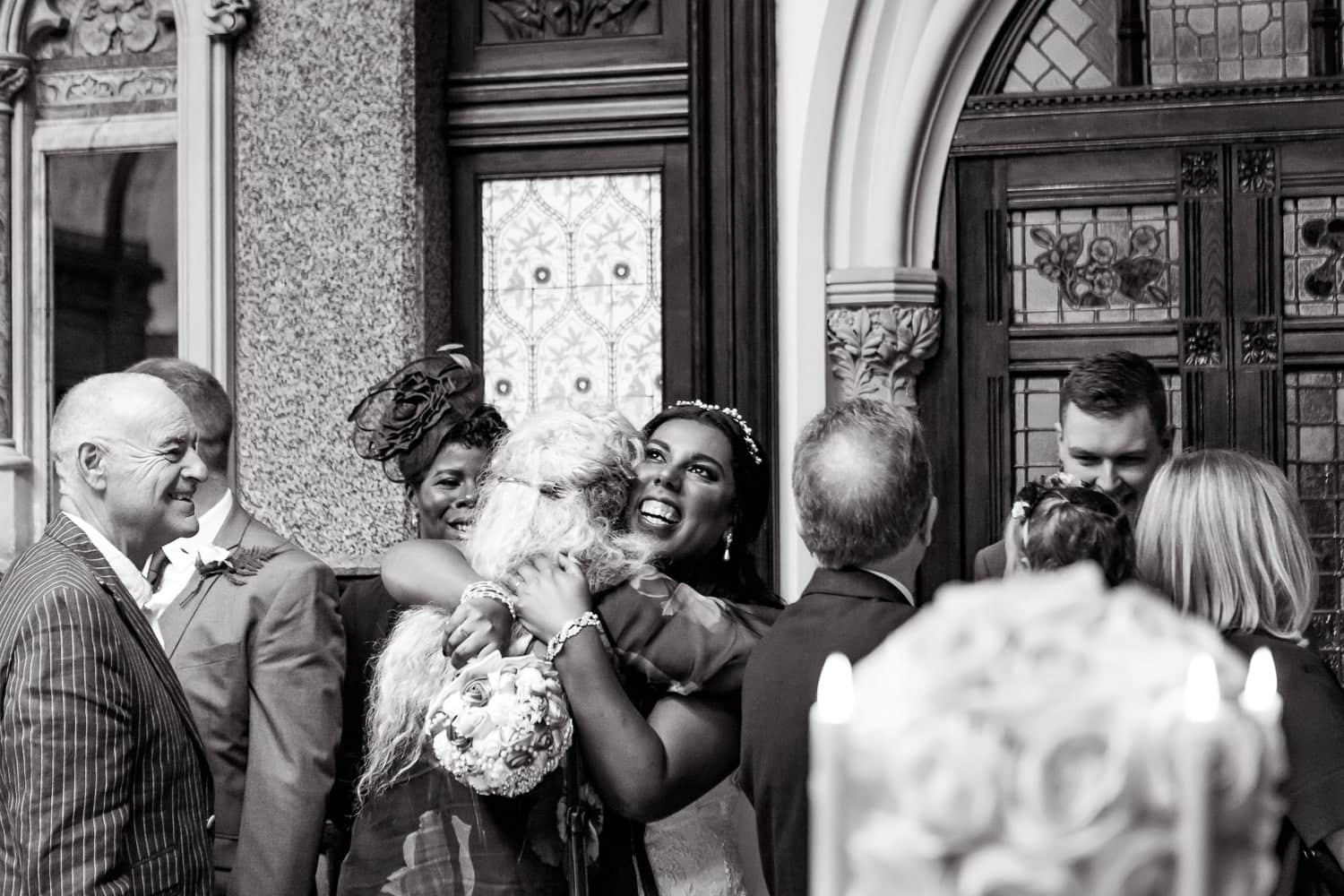 bride embraces a guests with a look of deep love on her face