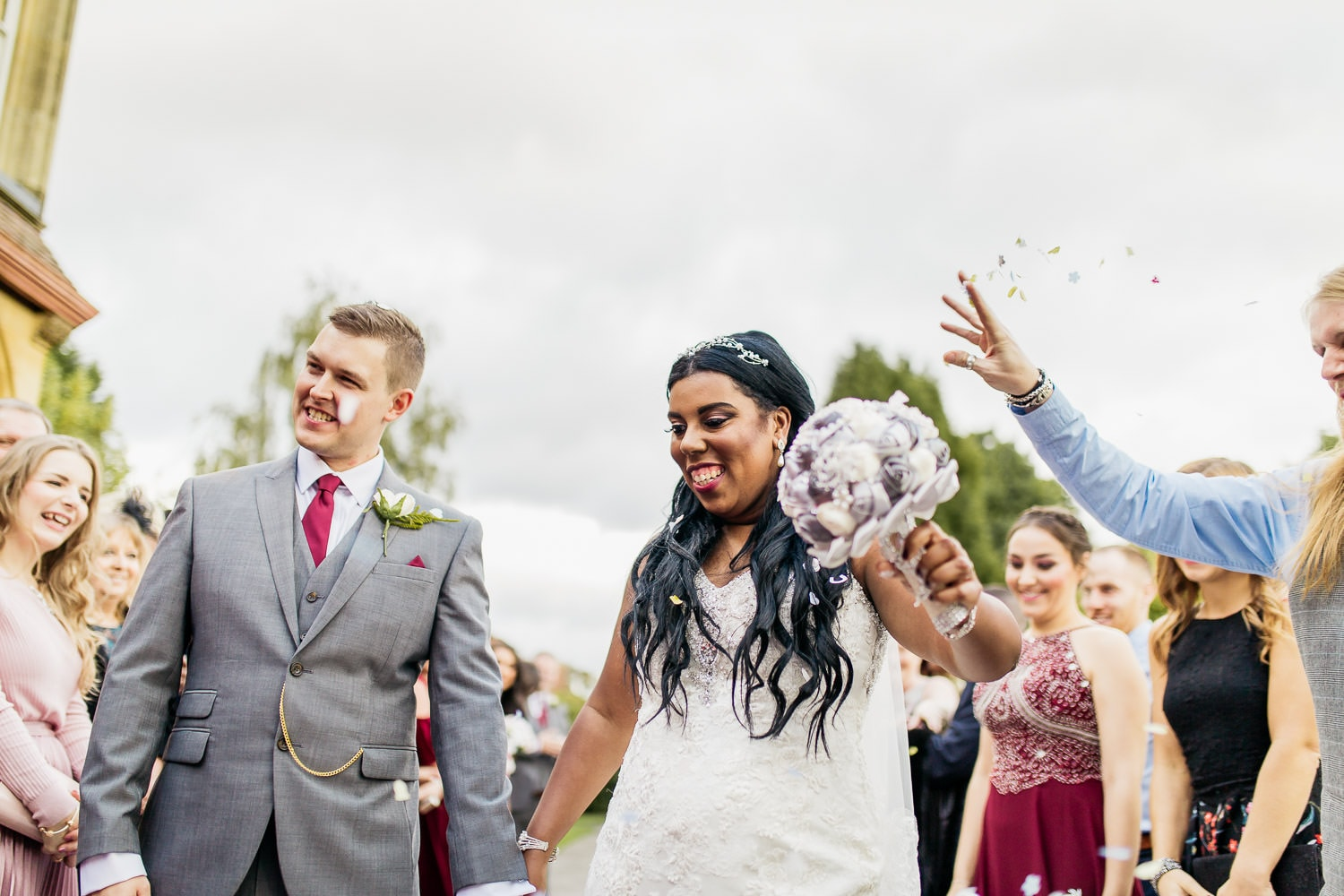 bride and groom having confetti thrown at them