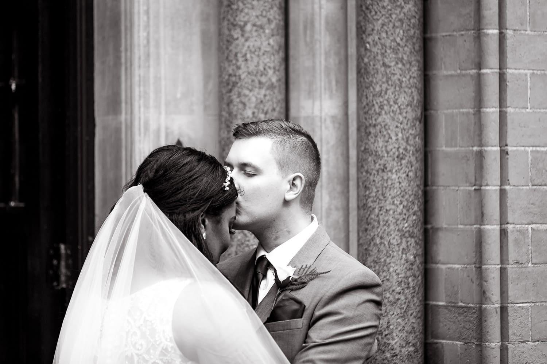 Highbury Hall Wedding photography captures groom gently kissing bride on her forehead