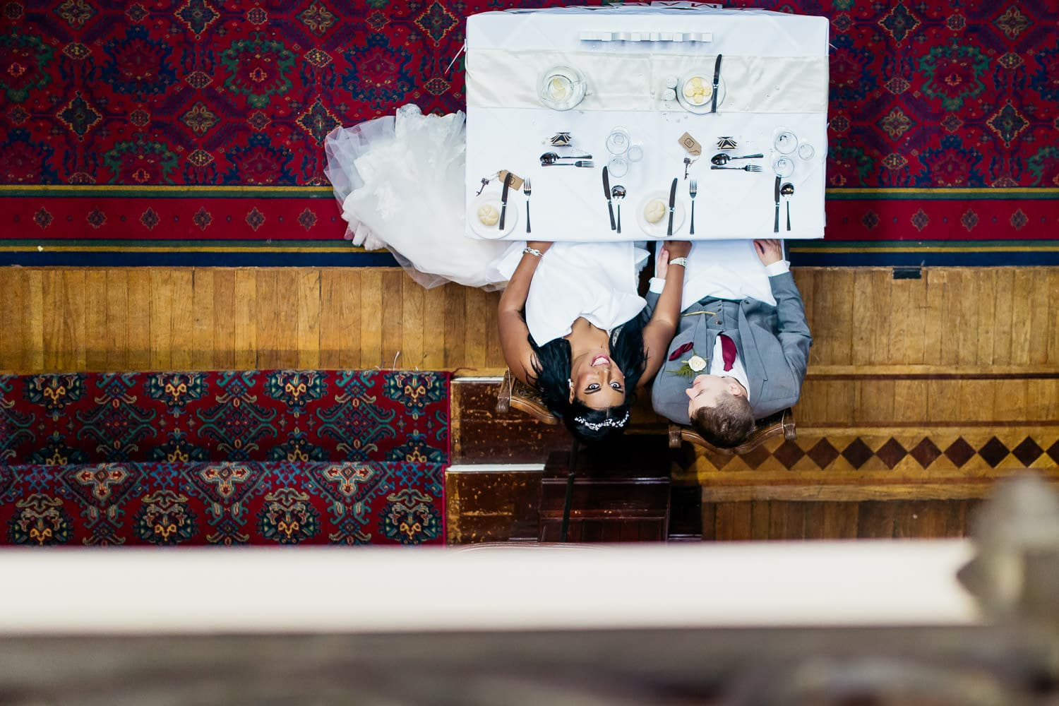 bride and groom look up at photographer standing above on balcony