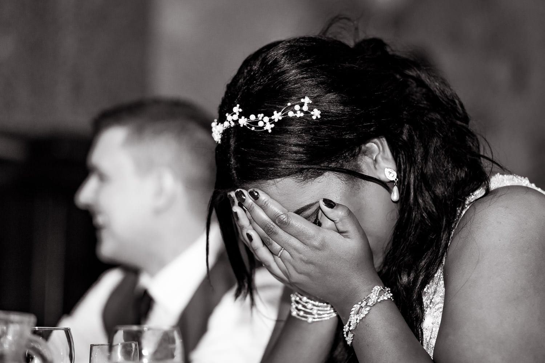 bride puts her face in her hands listening to embarrasing speech