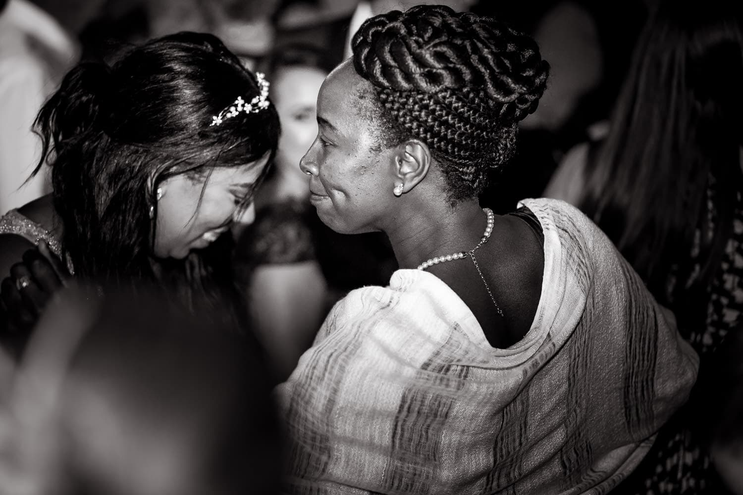 emotional bride and family member share a moment of the dancefloor
