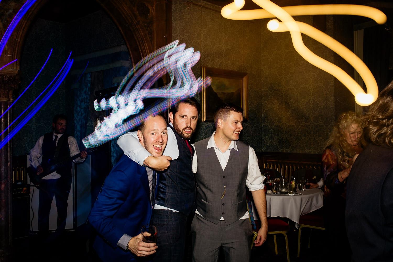 groom and groomsmen embrace on the dancefloor