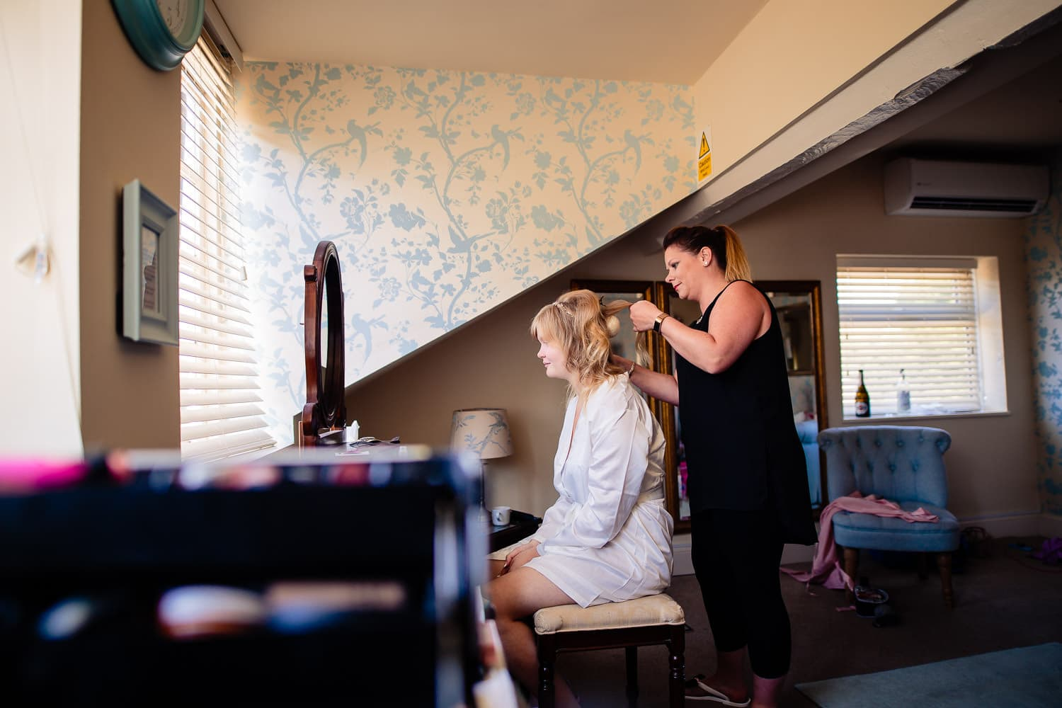 Warwick House Wedding Photography captures bride having hair done for wedding day