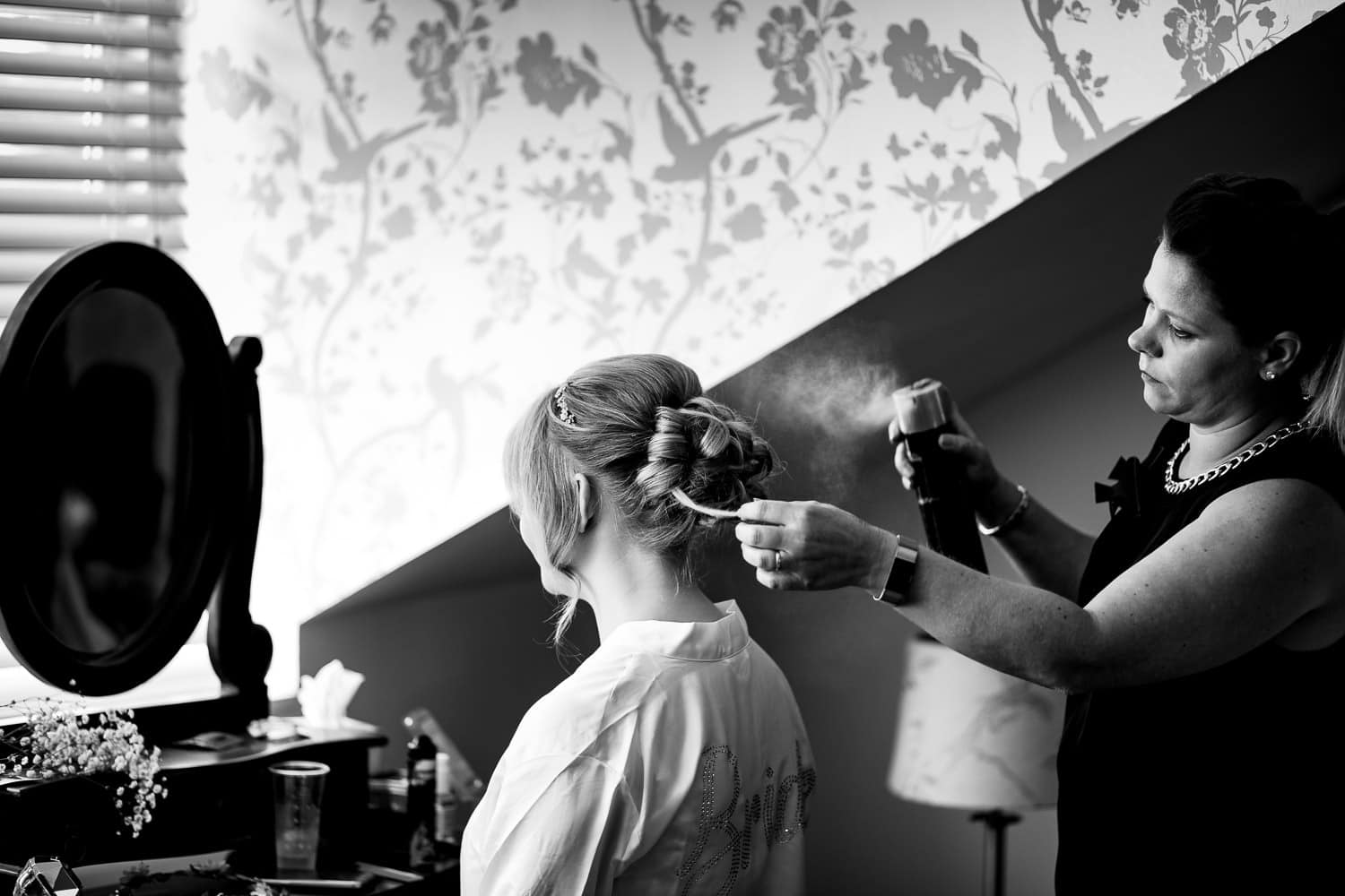Warwick House Wedding Photography captures bride having hairspray applied