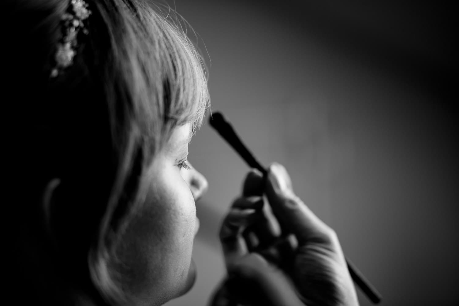 Warwick House Wedding Photography captures a beautiful picture of a bride having her makeup applied