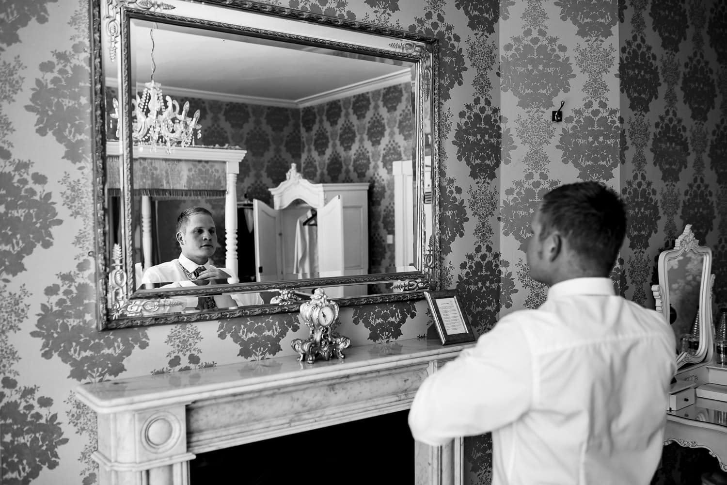 Reflection of groom in mirror captured by Warwick House Wedding Photography