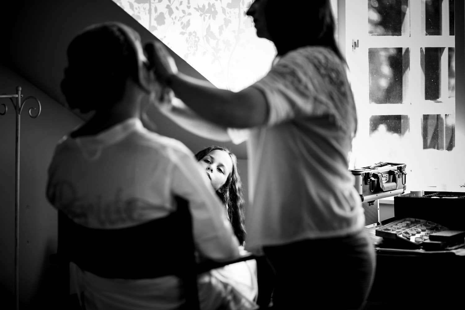 flower girls looks on while bride has makeup applied by Warwick House Wedding Photography