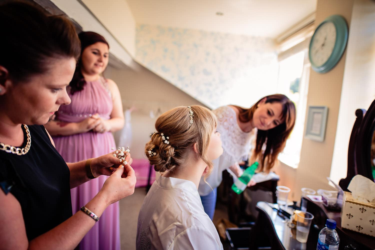 bridal party smile and share good times during preparations by Warwick House Wedding Photography