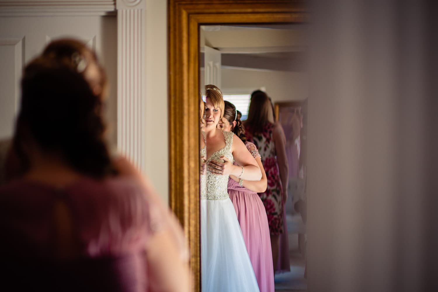 bride gets ready in her dress with help from bridesmaid by Warwick House Wedding Photography